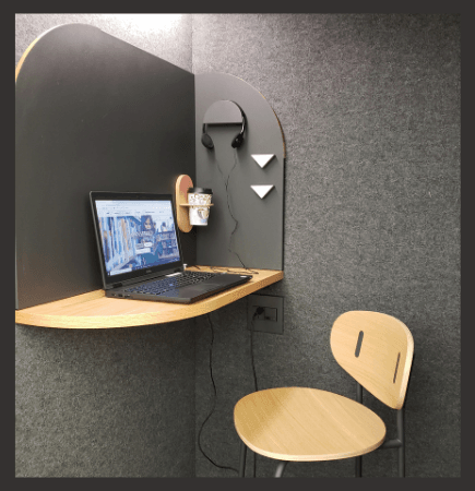 interior of a study booth with a laptop on a small table with a chair